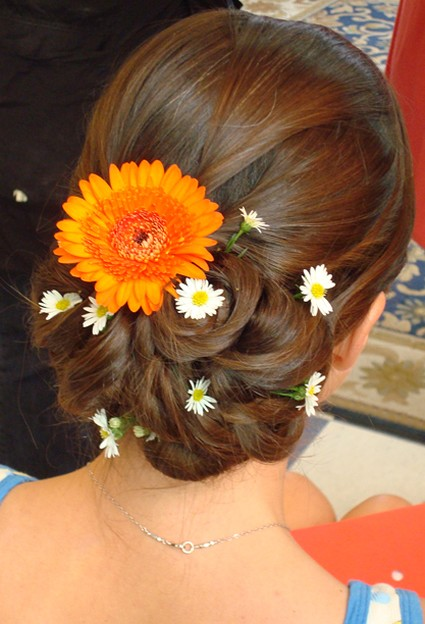 Beach wedding hairstyle updo with fresh flowers in orange and daisy
